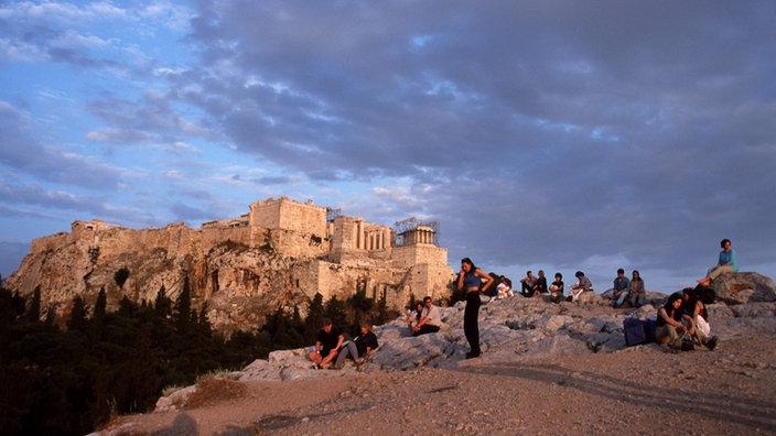 Steiniges Felsplateau mit Touristen, im Hintergrund die Akropolis