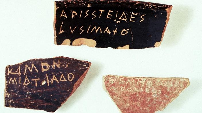 Drei Tonscherben – auf der obersten ist der Name 'Aristeides' eingeritzt.