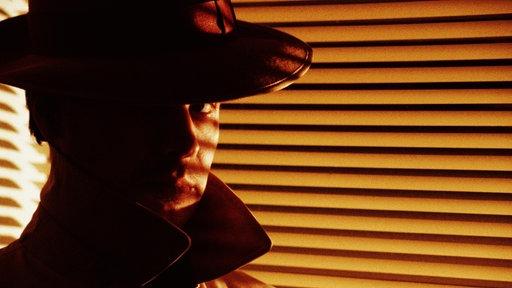 Ein Mann mit Hut und Trenchcoat steht im Halbschatten vor einem Fenster.