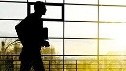 Der Schatten eines Mannes mit Aktentasche vor heller Fensterfront.
