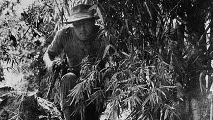 Legionär mit Gewehr im Dschungel.