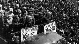 Rotgardisten fahren im Februar 1967 im offenen Wagen Menschen vor, die öffentlich als Staatsfeinde diskreditiert werden. Die Opfer müssen Spitzhüte mit ihrem Namen tragen.