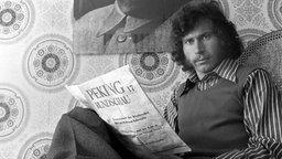 """Schwarzweißfoto: Paul Breiter sitzt auf einem Stuhl und liest in der """"Peking Rundschau""""."""