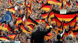 Helmut Kohl vor Deutschland-Flaggen 1990.