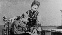 der sitzende Prinz Wilhelm und seine Mutter lesen ein Buch