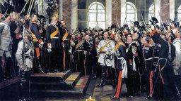 Der prachtvolle Spiegelsaal von Schloss Versailles. Gerade ist Wilhelm I. zum deutschen Kaiser ausgerufen worden. Jubelnde Generäle recken ihre Degen in die Luft. Der Kaiser steht auf einer Empore und empfängt die Huldigung mit ernster Mine. Hinter ihm werden Fahnen in die Höhe gehalten. In der Bildmitte steht Bismarck in weißer Uniform.