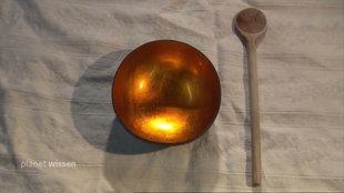 Leere goldene Schale und Kochlöffel auf einem weißen Tischtuch