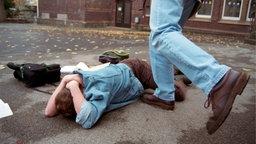 Ein Junge liegt auf dem Schulhof auf dem Boden, ein anderer Junge steht vor ihm und tritt ihn.