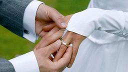 Der Bräutigam streift seiner Braut den Ehering über den Finger.