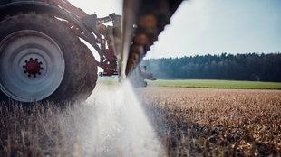 Nahaufnahme Traktor sprüht Glyphosat auf einem Feld.