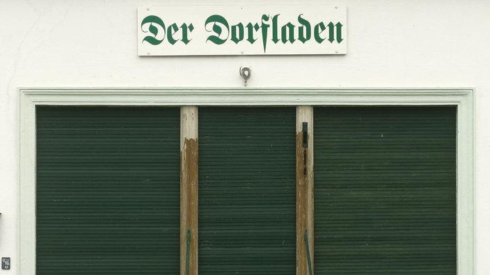 Blick auf einen geschlossenen Laden über dessen Eingangstür ein Schriftzug 'Der Dorfladen' prangt.