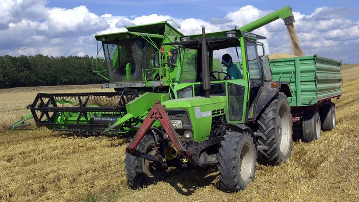Mähdrescher und Traktor bringen die Wintergerstenernte auf einem Feld in Thüringen ein.