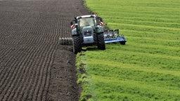Ein Traktor zieht einen Pflug über ein Feld.