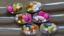 Verschiedene Tabletten und Kapseln auf Silberlöffeln.
