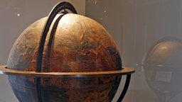Auf einem Flohmarkt ist auf einem Klappstuhl Trödel zusammengestellt. Farunter ist auch ein älterer Globus.
