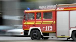 Ein rotes Feuerwehrfahrzeug mit der Rufnummernaufschrift 112 kommt von rechts. Es ist durch die Fahrgeschwindigkeit nur unscharf zu erkennen.