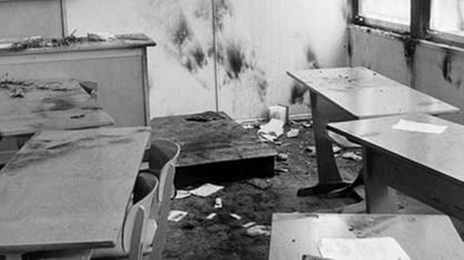 Fotografía en blanco y negro: aula con mesas y sillas de madera.  Mesas, paredes y ventanas muestran rastros de fuego y hollín.