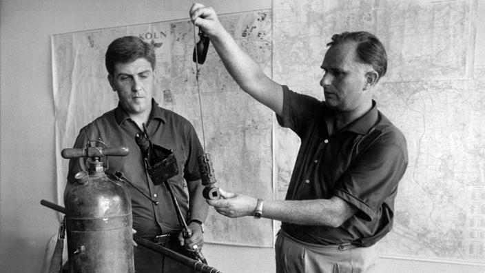 Fotografía en blanco y negro: dos detectives en su oficina con las armas y herramientas incautadas.