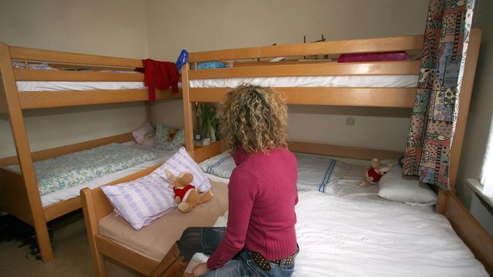 Una mujer está sentada en una habitación de refugio para mujeres frente a dos camas de dos pisos.