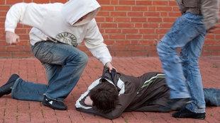 Jugendlicher schlägt auf einen anderen am Boden liegenden Jugendlichen ein, ein zweiter tritt zu