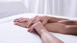 Hände liegen auf einem Bett
