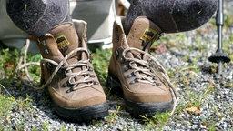 Ein Wanderer hat seine Schuhe ausgezogen, um die Fuesse nach einer Wanderung zu lueften. Seine Füße liegen auf seinen Trekkingschuhen auf