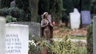 Blick über verschiedene Grabstellen. Inmitten von Grabsteinen steht eine Metallstatue, die eine betende Muttergottes darstellt.