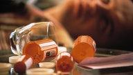 Verschiedene Behälter für Medikamente liegen geöffnet auf einem Tisch, Mann unscharf im Hintergrund