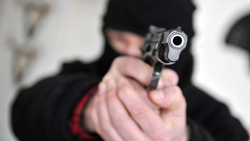 Ein Mann mit einer Maske über dem Kopf zielt in einer gestellten Szene mit seiner Waffe Richtung Kamera.