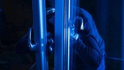 Ein Einbrecher öffnet nachts ein gekipptes Fenster