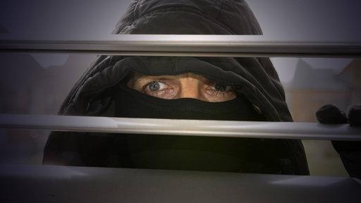Einbrecher schaut durch Rollläden