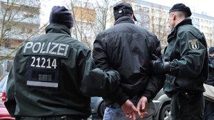Polizisten führen einen mit Handschellen gefesselten Mann zu einem Pkw. Der Mann gehört zu den acht Menschen, die nach Angaben der Polizei bei einem Großeinsatz gegen Drogendealer auf dem U-Bahnhof Heinrich-Heine-Straße in Berlin festgenommen wurden. Nach wochenlanger Videoüberwachung schlug die Polizei mit Einsatzkräften und Zivilfahndern zu.