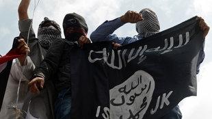 Vermummte Demonstranten halten eine Flagge des IS hoch.