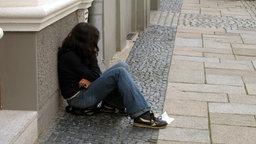Ein junges Mädchen sitzt bettelnd am Straßenrand.