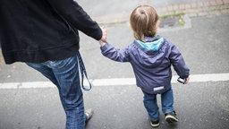 Mutter geht mit Sohn an der Hand