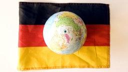 Eine Deutschlandfahne liegt auf weißem Untergrund; auf ihr ruht ein Globus.; Rechte: Imago