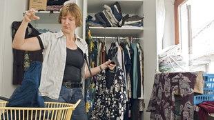 Eine Frau steht vor ihrem Kleiderschrank und sortiert aus.