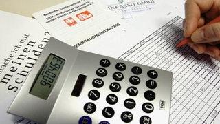 Taschenrechner, im Hintergrund Tabellen und Informationsmaterial zu Schulden und Insolvenz.