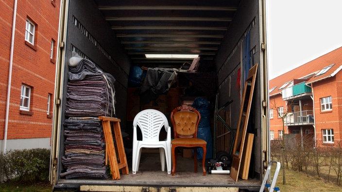 Blick in einen teilweise beladenen Möbelwagen einer Spedition, die einen Umzug organisiert.
