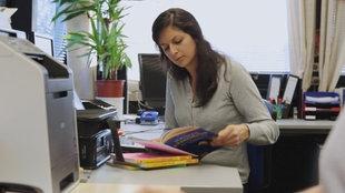 Frau sitzt im Büro am Schreibtisch