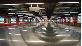 Blick in einen nahezu menschenleeren Gang der U-Bahn von Hongkong. Rechts und links beleuchtete Werbekästen, an der Decke zahlreiche Neonröhren, die sich auf dem Boden spiegeln