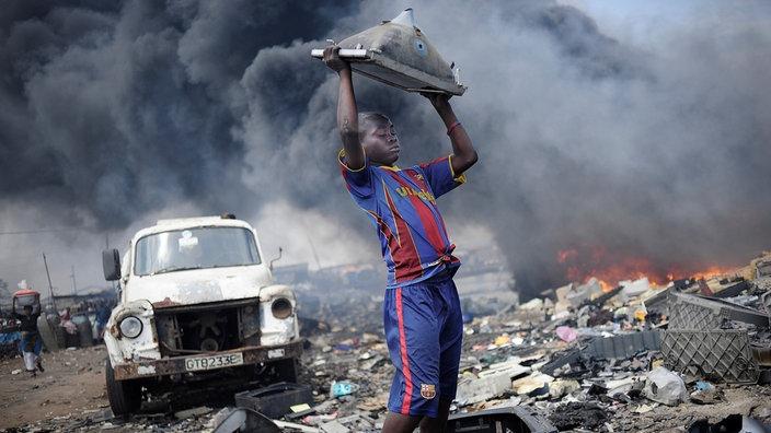 Ein Junge hebt auf der Giftmüllhalde Agbogbloshie in Ghana einen alten Monitor nach oben, hinter ihm toxischer Rauch.