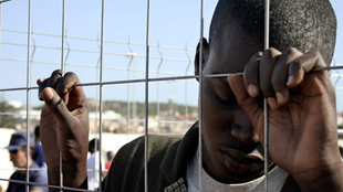 Ein junger Afrikaner lehnt seinen Kopf an einen Drahtzaun.