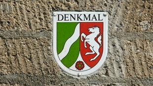 In einer alten Mauer ist eine Plakette eingelassen, auf der der Schriftzug Denkmal sowie das Wappen von NRW zu sehen sind.