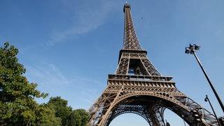 Der Blick fällt auf dem Eiffelturm vor einem strahlend blauen Himmel.