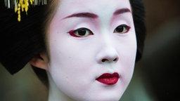 Porträt einer Geisha, die traditionell geschminkt ist