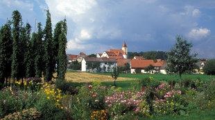 Kleines Dorf liegt eingebettet in blühender Lanschaft unter blauem Himmel