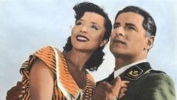 Die beiden Darsteller Sonja Ziemann und Rudolf Prack stehen Arm in Arm nebeneinander und schauen in die Ferne.; Rechte: dpa/picture-alliance