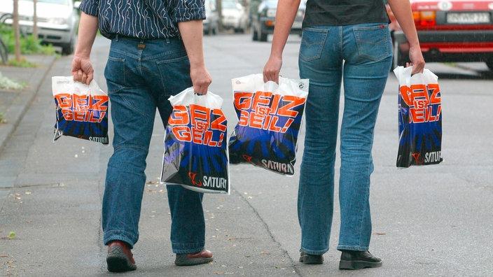 """Personas con bolsas de plástico en las que """"La avaricia es genial"""" dice"""