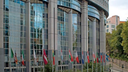 Vor der Glasfassade des Europäischen Parlaments hängen die Flaggen der Mitgliedsländer.